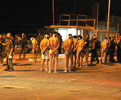 IDF soldiers checking Fatah men who fled clashes with Hamas at the Gaza crossing before dawn Sunday.- David Boymovitch