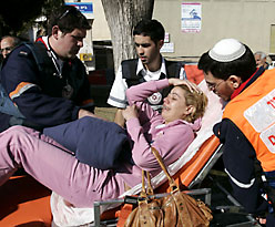 Medics evacuating a woman suffering from shock after a Qassam rocket struck the Negev town of Sderot on Wednesday. (Reuters)