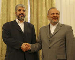 Hamas leader Khaled Meshal, left, standing with Iranian Foreign Minister Manouchehr Mottaki, after a news conference in Tehran. (AP)
