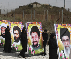 Lebanese women holding pictures of Shi'ite leaders, including Iran's Khomeini, as they mark 'Al-Quds Day' near the border with Israel. (AP)