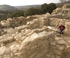 Archeologist Yossi Garfinkel crouching Sun. at dig near Beit Shemesh where pottery was unearthed that may bear oldest Hebrew writing ever found. (AP)