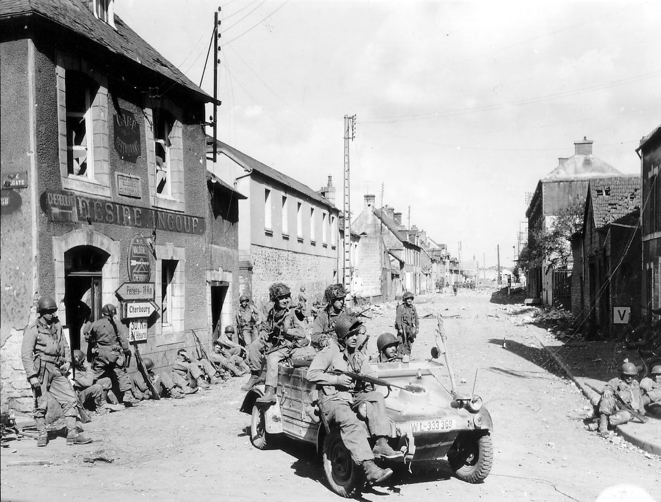 American paratroopers of the 101st Airborne Division driving a commandeered German vehicle in Carentan, June 1944.